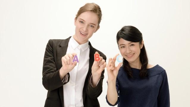 外国人教師と生徒が手にABCの形をした模型を持っている